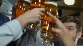 Compañía de los vidrios de cerveza de la gente que tintinean feliz, relajándose con los amigos el fin de semana almacen de metraje de vídeo