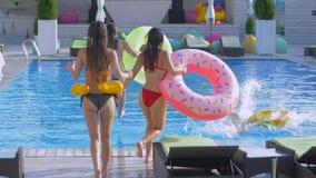 Compañía de muchachas alegres bien proporcionadas en trajes de baño con los anillos inflables funcionados con en fila y salto en  almacen de video