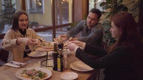 Compañía de tres amigos que comen la pizza sabrosa y que beben el vino en café italiano moderno en la tabla Dos mujeres jovenes y almacen de video