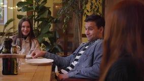 Compañía de tres amigos que comen la pizza sabrosa y que beben el vino en café italiano moderno en la tabla Dos mujeres jovenes y almacen de metraje de vídeo