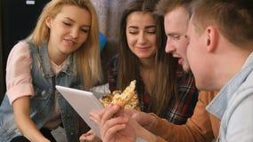 Compañía del estudiante que come la pizza y que usa la tableta en casa Imagen de archivo