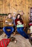 Compañía del muchacho y de dos muchachas con los regalos en el cuarto con de madera Foto de archivo