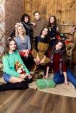 Compañía del muchacho y de seis muchachas con los regalos en el cuarto con de madera Imagen de archivo