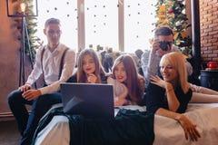 Compañía en cama con un ordenador portátil, Año Nuevo, celebración, atmósfera casera foto de archivo libre de regalías