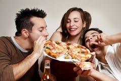 Compañía feliz de la juventud que come una pizza Foto de archivo libre de regalías