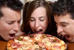 Compañía feliz de la juventud que come una pizza Imágenes de archivo libres de regalías