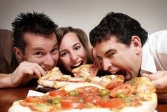 Compañía feliz de la juventud que come una pizza Imagen de archivo libre de regalías