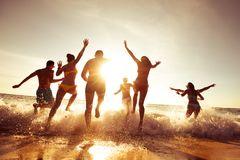 Compañía grande de los amigos que se divierten en la playa de la puesta del sol Fotos de archivo