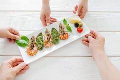 Compañía que cena en el restaurante, compartiendo la comida Fotografía de archivo