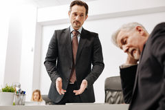 Compañero de trabajo desconcertado que tiene dificultades en la conversación con el colega fotos de archivo