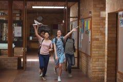 Compañeros de clase emocionados que corren con las tarjetas del grado en pasillo Foto de archivo