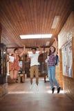 Compañeros de clase emocionados que saltan con las tarjetas del grado en pasillo Imagenes de archivo