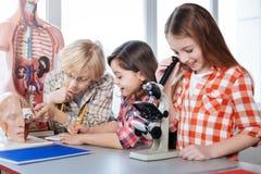 Compañeros de clase productivos que trabajan en la asignación de la biología Fotografía de archivo