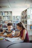 Compañeros de clase que hacen la preparación en biblioteca Imagen de archivo
