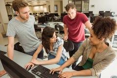 Compañeros de clase que trabajan junto en la sala de ordenadores Fotos de archivo libres de regalías