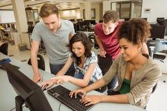 Compañeros de clase que trabajan junto en la sala de ordenadores Fotos de archivo