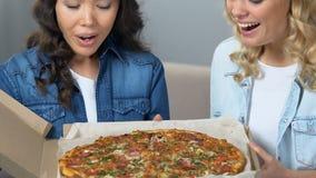 Compañeros de cuarto alegres que abren la caja con la pizza, muchachas que disfrutan del aroma, partido de gallina almacen de video