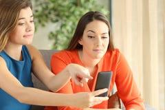 Compañeros de cuarto decepcionados que miran medios en un teléfono Imagen de archivo
