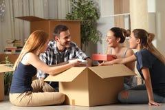 Compañeros de cuarto felices unboxing las pertenencia que se mueven a casa fotografía de archivo