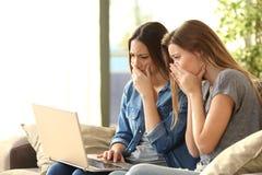Compañeros de cuarto preocupantes en línea con un ordenador portátil Fotos de archivo libres de regalías