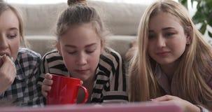 Compañeros de cuarto que miran el contenido de los medios en el ordenador portátil mientras que comiendo café y palomitas almacen de video
