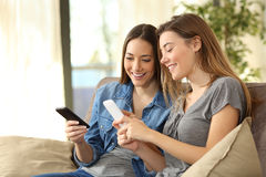 Compañeros de cuarto que usan los teléfonos elegantes en casa Fotografía de archivo