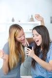 Compañeros de cuarto sorprendentes que miran ofertas en línea con el teléfono elegante Fotos de archivo libres de regalías