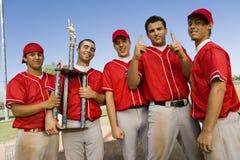 Compañeros de equipo del béisbol que sostienen el trofeo Imagen de archivo libre de regalías