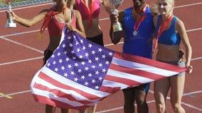 Compañeros de equipo que saltan feliz con los trofeos y la bandera americana, orgullo nacional almacen de video