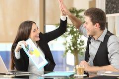 Compañeros de trabajo acertados que celebran buenos resultados fotografía de archivo libre de regalías