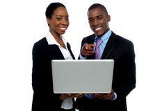 Compañeros de trabajo africanos que funcionan la computadora portátil y señalar Fotos de archivo libres de regalías