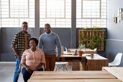 Compañeros de trabajo africanos sonrientes que toman una rotura en una oficina moderna Foto de archivo