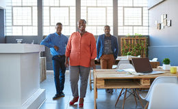Compañeros de trabajo africanos sonrientes que toman una rotura en una oficina moderna Imágenes de archivo libres de regalías