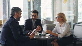 Compañeros de trabajo alegres en la sonrisa que habla de la ropa formal en café durante hora de la almuerzo metrajes