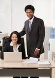 Compañeros de trabajo con la computadora portátil en el escritorio Foto de archivo libre de regalías