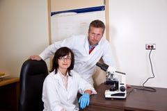 Compañeros de trabajo de los científicos cerca por el microscopio Fotos de archivo libres de regalías