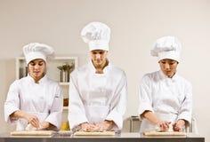 Compañeros de trabajo del cocinero que amasan la pasta en cocina Fotos de archivo