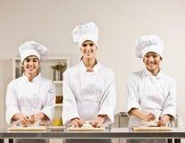 Compañeros de trabajo del cocinero que amasan la pasta en cocina fotografía de archivo libre de regalías