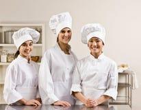 Compañeros de trabajo del cocinero que presentan en cocina comercial Imagen de archivo