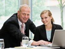 Compañeros de trabajo del hombre de negocios y de la hembra con la computadora portátil Foto de archivo libre de regalías