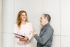 Compañeros de trabajo del negocio que hablan en vestíbulo Imagen de archivo
