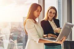 Compañeros de trabajo elegantes sonrientes que sostienen un ordenador portátil que discute las nuevas ideas que se colocan en ofi Foto de archivo libre de regalías