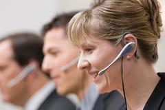 Compañeros de trabajo en los receptores de cabeza que trabajan en centro de atención telefónica Fotografía de archivo