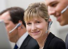 Compañeros de trabajo en los receptores de cabeza que trabajan en centro de atención telefónica Imagenes de archivo