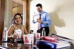 Compañeros de trabajo en oficina que comen el alimento para llevar chino foto de archivo