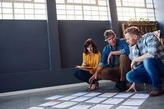 Compañeros de trabajo enfocados que discuten el papeleo presentado en un piso de la oficina Fotos de archivo