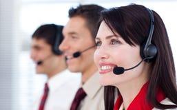 Compañeros de trabajo felices con los receptores de cabeza encendido Imagen de archivo