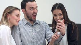 Compañeros de trabajo jovenes de la oficina que se divierten que toma selfies en el teléfono almacen de video