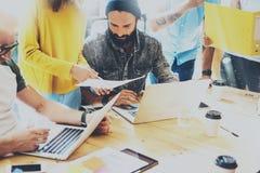 Compañeros de trabajo jovenes del grupo que toman grandes decisiones económicas Desván moderno creativo del estudio de Team Discu imagen de archivo