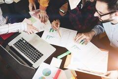 Compañeros de trabajo jovenes que discuten las cartas y los gráficos que muestran los resultados de su trabajo en equipo acertado Foto de archivo libre de regalías